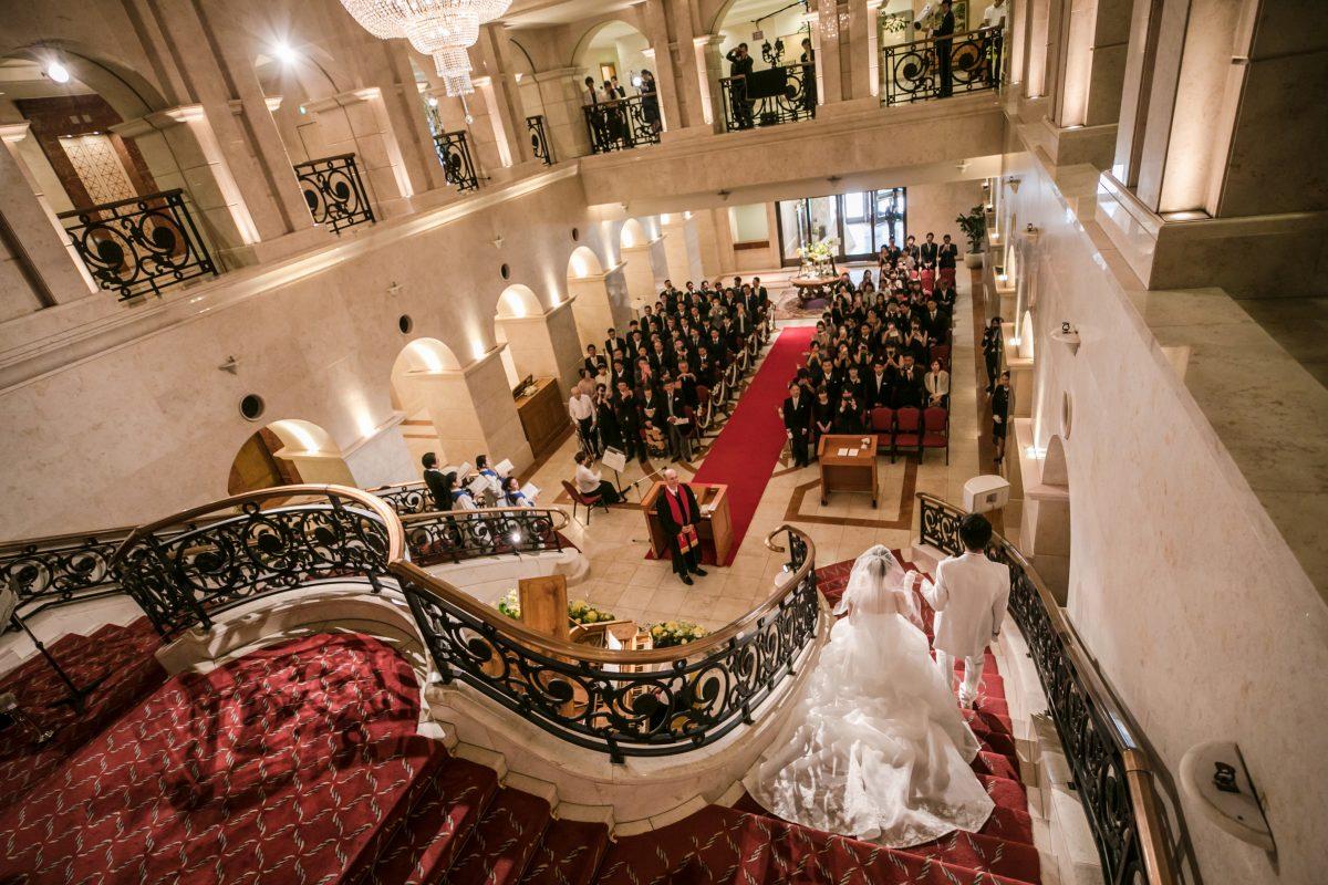 楽器の生演奏と聖歌隊の歌声に包まれ大階段を進む新郎新婦